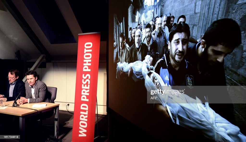 World Press Photo jury president Santiago Lyon (L) and Managing Director of World Press Photo Michael Munneke are pictured during the announcement of the contest's winning photo (seen at right) in Amsterdam on February 15, 2013. Photographer Paul Hansen from Sweden won the 56th World Press Photo Contest with a picture of men carrying the bodies of two dead children in Gaza City. AFP PHOTO / ANP / LEX VAN LIESHOUT -netherlands out - belgium out-