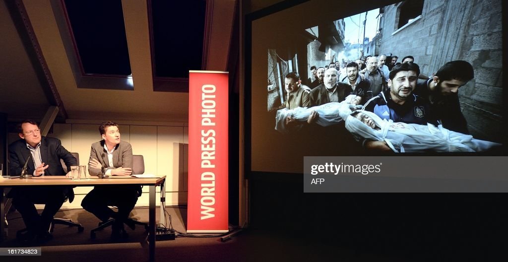 World Press Photo jury president Santiago Lyon (L) and Managing Director of World Press Photo Michael Munneke look at the contest's winning photo during the annoucement of it in Amsterdam on February 15, 2013. Photographer Paul Hansen from Sweden won the 56th World Press Photo Contest with a picture of men carrying the bodies of two dead children in Gaza City. AFP PHOTO / ANP / LEX VAN LIESHOUT -netherlands out - belgium out-
