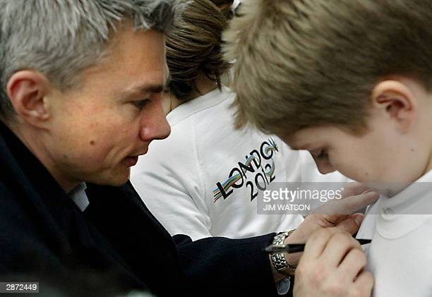 World Record triple jumper Jonathan Edwards signs his autograph to a boy's jersey 16 January 2003 at the Royal Opera House during the 2012 Launch...