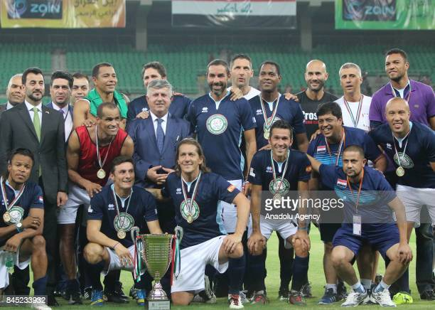 World Stars team and officials pose for a photo with a trophy after a friendly match between Iraq Stars and World Stars at the Basra International...