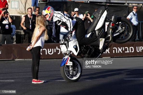 World stunt riding champion Chris Pfeiffer kisses an Israeli girl as he performs a trick on his superbike below the ancient walls of Jerusalem's Old...