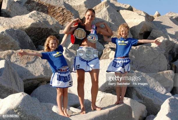 World Thai kickboxing champion Julie Kitchen with her belts and twin eight year old daughters Allaya and Amber on the rocks alongside Long Rock beach...