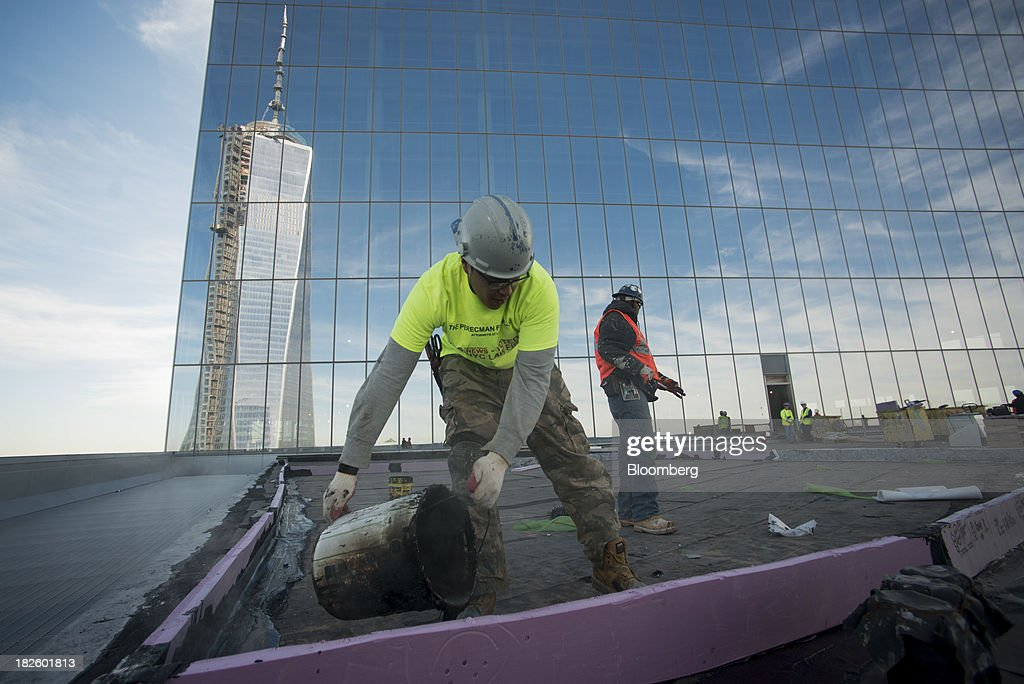 1 World Trade Center stands as contractors waterproof the 48th floor of the 4 World Trade Center building, managed by Silverstein Properties Inc., in New York, U.S., on Wednesday, Sept. 25, 2013. Real estate developer Larry Silverstein cant recoup any of the $1.2 billion recovered by World Trade Center insurers in settlements with airlines and airport security companies over the Sept. 11, 2001, terrorist attack that destroyed the office complex, a judge ruled. Photographer: Craig Warga/Bloomberg via Getty Images