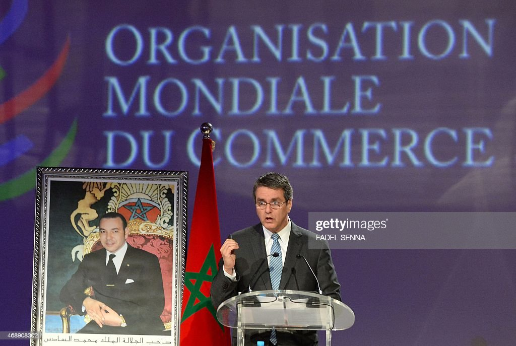 World Trade Organisation (WTO) Director General, Roberto Azevedo, stands next to a portrait of Moroccan King Mohammed VI as he delivers a speech during a ceremony marking the 20th anniversary of the WTO in the Moroccan city of Marrakesh where it was created, on april 8, 2015.