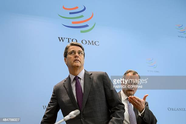 World Trade Organisation directorgeneral Brazil's Roberto Azevedo arrives flanked by WTO spokesman US Keith Rockwell to give a press conference on...