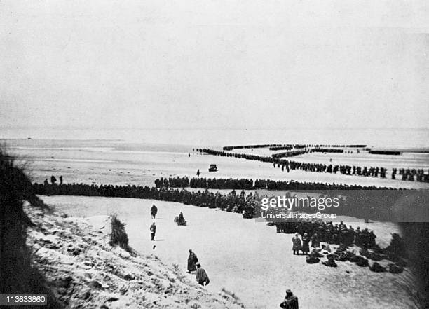 World War 2 British retreat from Dunkirk British troops forming into winding queues waiting to board small boats which ferried them to larger vessels...