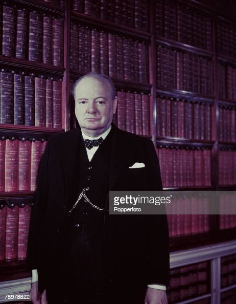 World War II March 1945 A portrait of British Prime Minister Winston Churchill standing by a row of book shelves