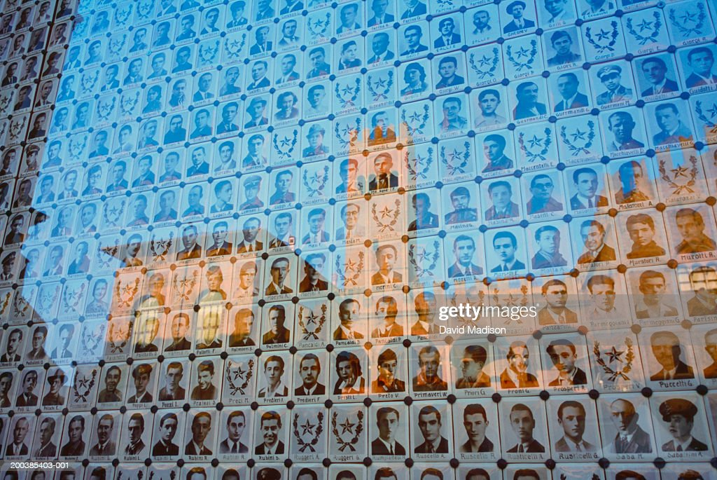 World War II Partisan memorial wall and reflection of Palazzo Enzo Re : Stock Photo