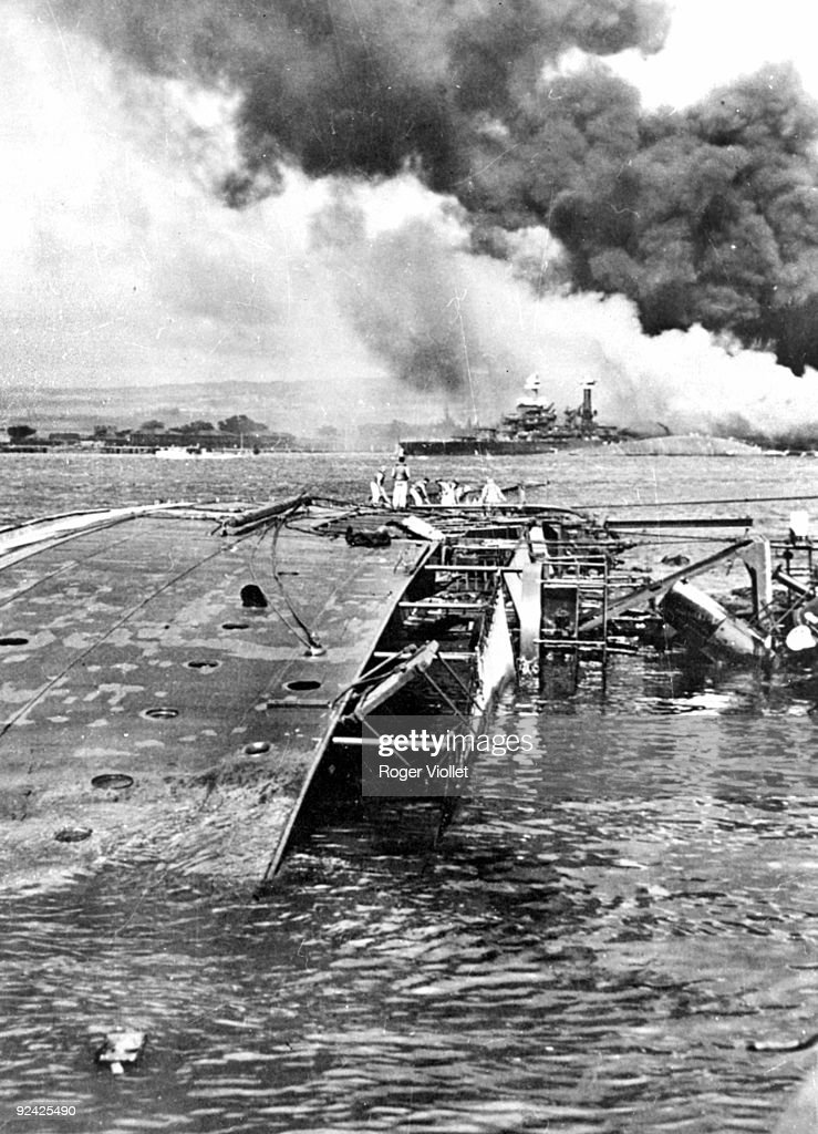 """the background of the pearl harbor attack in 1941 """"photo [of] the destroyer[s] uss cassin and uss downes in drydock with the battleship uss pennsylvania in the background after the japanese attack on pearl harbor, december 7, 1941,""""."""