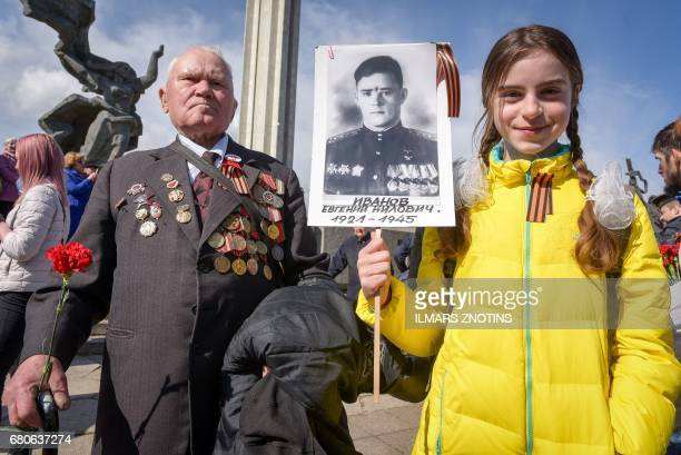 A World War II veteran and a girl attend festivities at the Victory Monument as Latvia's large Russian minority marks 72 years since the end of World...