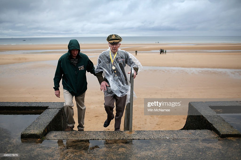 World War II veteran Charles Alford of the 6th Armor Division, from Waco, Texas, climbs the stairs with his son David on Omaha Beach where he landed as part of the invasion of Normandy June 4, 2014 in Vierville-Sur-Mer, France. June 6th is the 70th anniversary of the D-Day landings which saw 156,000 troops from the allied countries including the United States and the United Kingdom join forces to launch an attack on the beaches of Normandy, these assaults are credited with the eventual defeat of Nazi Germany. A series of events commemorating the 70th anniversary is planned for the week with many heads of state travelling to the famous beaches to pay their respects to those who lost their lives.