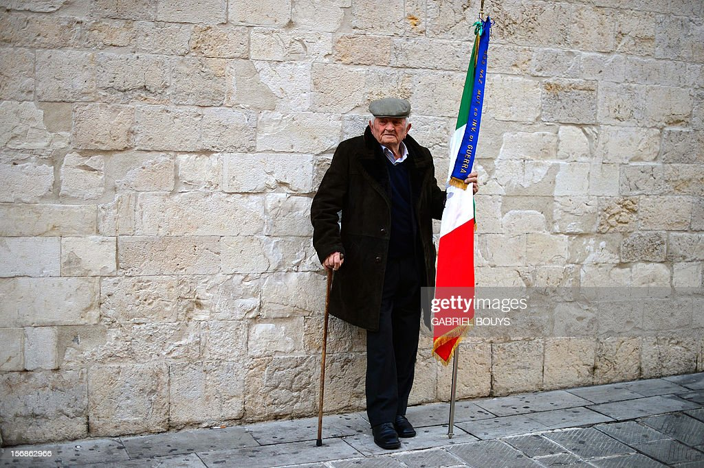 A World War II veteran holds a national Italian flag while waiting prior to attend a ceremony in Gualdo Tadino, on November 23, 2012, in honor of French Minister for Culture and Communication's grand-father born in this village in Umbria. French Minister Aurelie Filippetti's grand-father, Tommaso, was an anti-fascist Italian who migrated to France and died in the Bergen-Belsen concentration camp in 1945. Aurelie Filippetti was honored as Citizen of Honor of Gualdo Tadino as part of this ceremony. AFP PHOTO / GABRIEL BOUYS