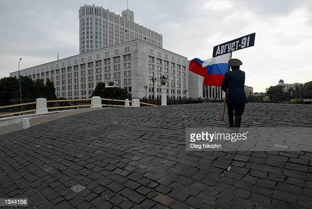 World War II veteran Lev Gitsevich 74 holds a Russian flag while on his way to a celebration of the 11th anniversary of the failed Communist coup...