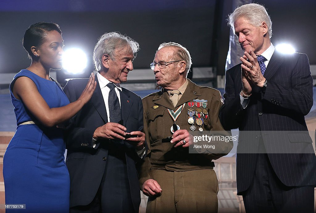 World War II veteran Scottie Ooton (3rd L) who helped to liberate a concentration camp and Holocaust survivor and author Elie Wiesel (2nd L) are presented with pins as presenters former U.S. President Bill Clinton (R) and museum staff Rebecca Dupas (L) look on during the 20th anniversary National Tribute at the United States Holocaust Memorial Museum April 29, 2013 in Washington, DC. The Museum was hosting a two-day tribute event to honor Holocaust survivors and World War II veterans to mark its 20th anniversary.