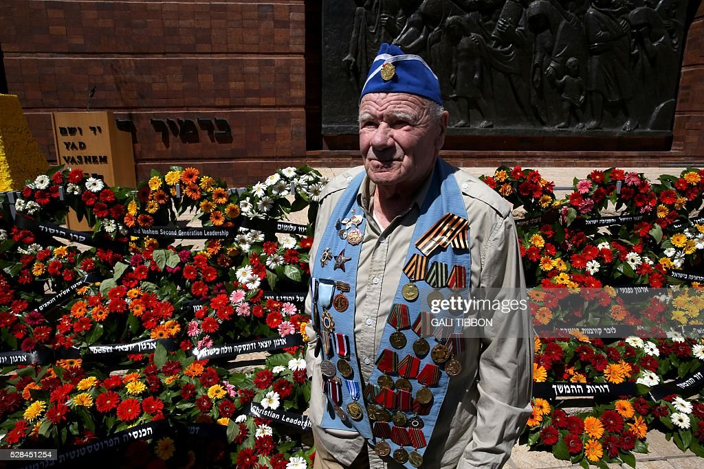 A World War II veteran stands next to wreaths during the annual Holocaust Remembrance Day ceremony at the Yad Vashem Holocaust Memorial in Jerusalem on May 5, 2016. The state of Israel marks the annual Memorial Day commemorating the six million Jews murdered by the Nazis in the Holocaust during World War II. / AFP / GALI