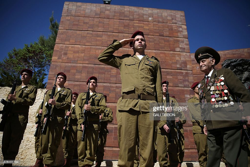 A World War II veteran walks past an honour guard of Israeli soldiers during the annual Holocaust Remembrance Day ceremony at the Yad Vashem Holocaust Memorial in Jerusalem on May 5, 2016. The state of Israel marks the annual Memorial Day commemorating the six million Jews murdered by the Nazis in the Holocaust during World War II. / AFP / GALI
