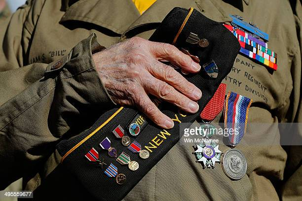 World War II veteran William Spriggs who took part in the invasion of Normandy places his medalcovered hat over his heart during the playing of...