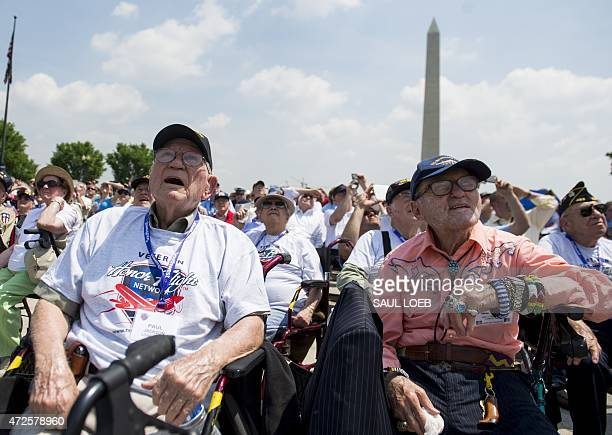 World War II veterans and their families watch as dozens of World War II era military airplanes fly over the National World War II Memorial on the...