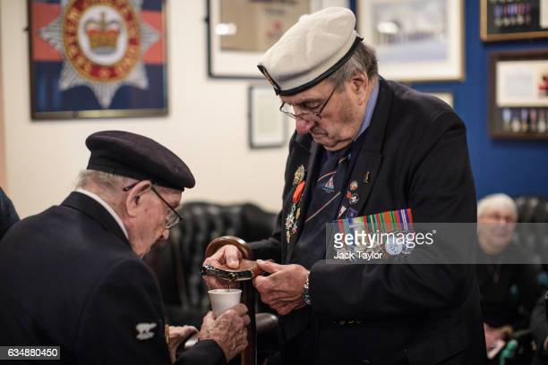 World War II veterans Harry Card pours some liquor into Joe Hadley's coffee ahead of a photo call for the launch of the Veterans Black Cab ride at...