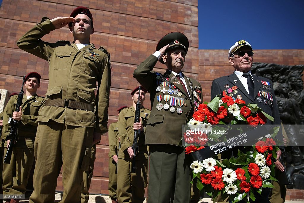 World War II veterans hold a wreath as they stand next to an honour guard of Israeli soldiers during the annual Holocaust Remembrance Day ceremony at the Yad Vashem Holocaust Memorial in Jerusalem, on May 5, 2016. The state of Israel marks the annual Memorial Day commemorating the six million Jews murdered by the Nazis in the Holocaust during World War II. / AFP / GALI