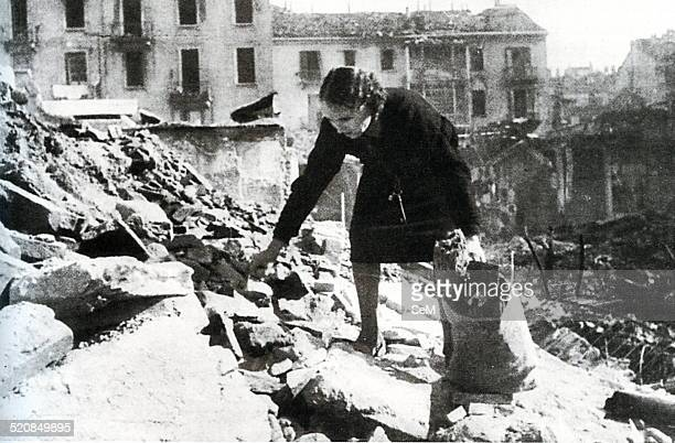 World War IIItalian Fascism 1944 1945Bombing in Italy A woman tries to recover some pieces of wood to burn in the midst of the rubble of a bombed...