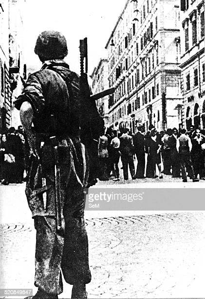 World War IIWar in Italy Rome 1944 A German paratrooper armed with a submachine gun during a roundup of civilians in the streets of Rome occupied