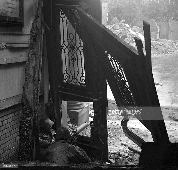 World War Two Aachen Germany 18th October American soldiers firing at Germans from a machine gun nest in shattered building during street fighting in...