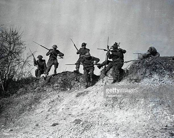World War Two England November British army soldiers holding rifles making a bayonet charge over rough country terrain during military training...