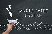 Man holding paper ship on blackboard with text: World wide cruise