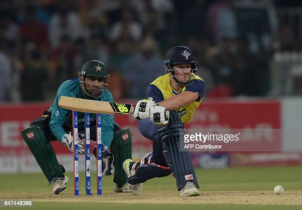 World XI batsman David Miller plays a shot as Pakistani captain and wicketkeeper Sarfraz Ahmad looks on during the third and final Twenty20...