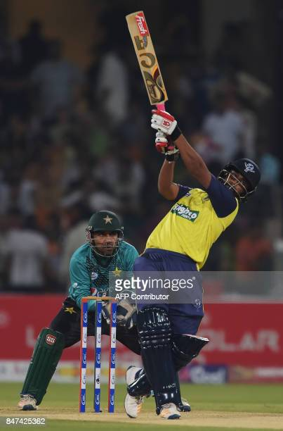 World XI batsman Tamim Iqbal hits a shot as Pakistani captain and wicketkeeper Sarfraz Ahmad looks on during the third and final Twenty20...