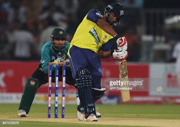 World XI batsman Tamim Iqbal plays a shot as Pakistani captain and wicketkeeper Sarfraz Ahmad looks on during the third and final Twenty20...