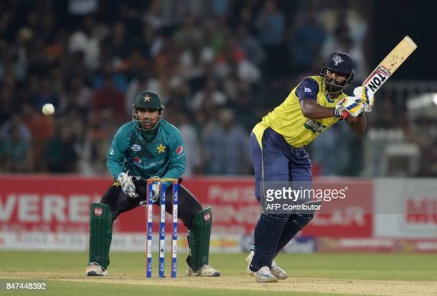 World XI batsman Thisara Perera plays a shot as Pakistani captain and wicketkeeper Sarfraz Ahmad looks on during the third and final Twenty20...