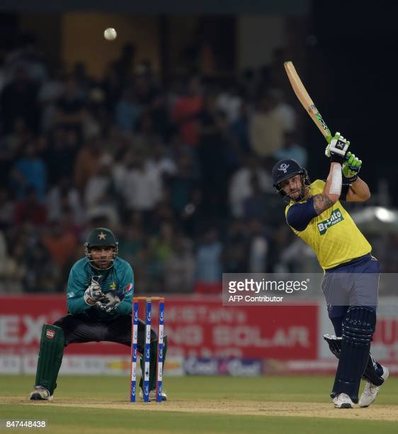 World XI captain Faf du Plessis hits a shot as Pakistani captain and wicketkeeper Sarfraz Ahmad looks on during the third and final Twenty20...