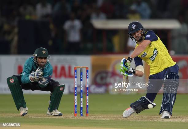 World XI cricket captain Faf du Plessis plays a shot as Pakistani captain and wicketkeeper Sarfraz Ahmad looks on during the second Twenty20...