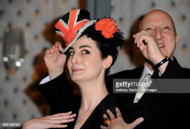 Worldrenowned milliner Stephen Jones joins model Erin O'Connor as she models a brightly coloured couture hat at the Victoria and Albert Museum in...