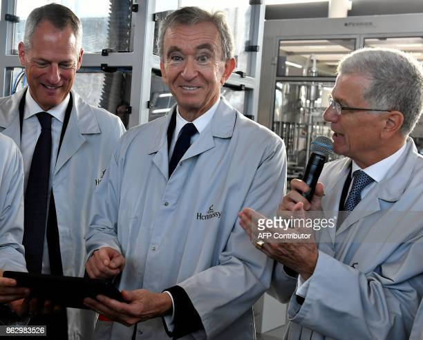 World's biggest luxury goods company LVMH's CEO Bernard Arnault 'Moet Hennessy' CEO Philippe Schaus and 'maison Hennessy' CEO Bernard Peillon laugh...