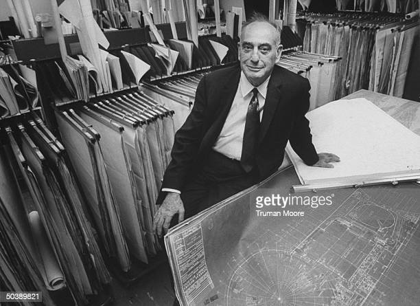 World's Fair Corp Pres Robert Moses sitting with blueprints for various fair buildings
