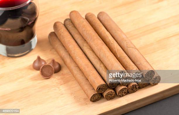 Worldwide famous Cuban cigars over wood with chocolates and red wine hand rolled natural habanos an unhealthy tradition in the Caribbean Island
