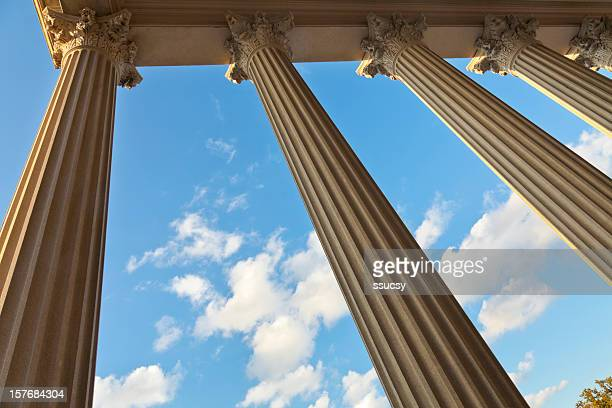 Worm's eye view of majestic columns framing sky and clouds