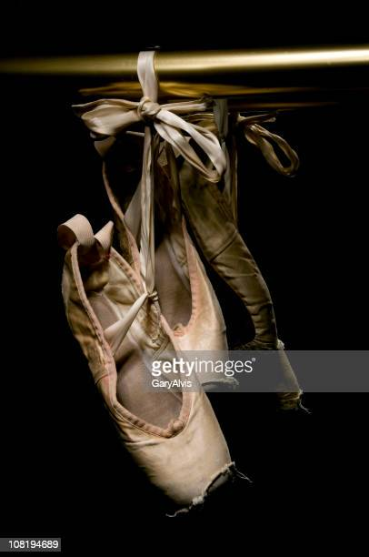 Worn Ballet Shoes Hanging on Brass Rail, Low Key
