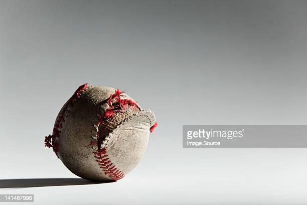 Worn baseball with broken stitching
