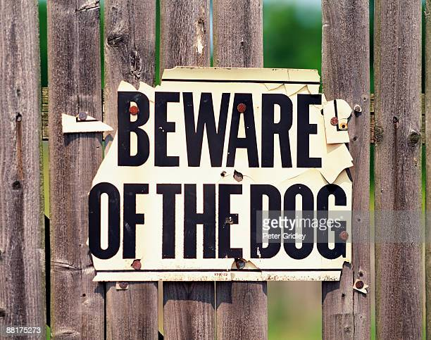 Worn Beware of dog sign on fence