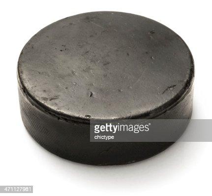 Worn black hockey puck on white background
