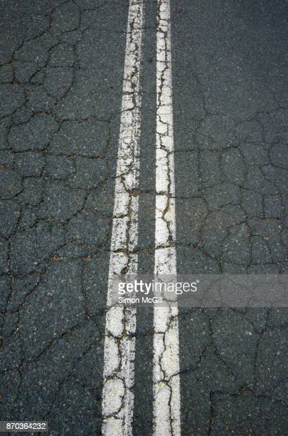 Worn, cracked asphalt and painted white double dividing lines on a road