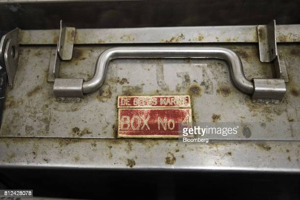 A worn sign reading 'De Beers Marine Box No 4' sits on a case used to transport sealed cans of diamonds from ship to shore in a storage rack aboard...