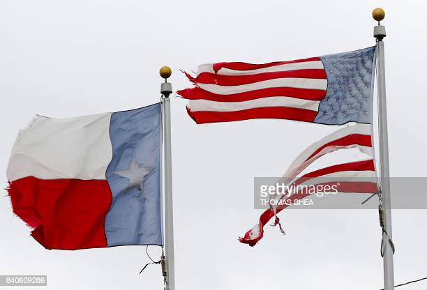 A worn US flag and Texas State flag blow in the wind in Pearland Texas on August 29 2017 as the city battles with the aftermath of storm Harvey and...