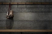 Spotlit old vintage boxing gloves hanging on a hanger above an empty wooden bench in a locker change room - 3D render