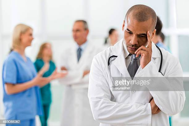 Worried African American doctor thinking.