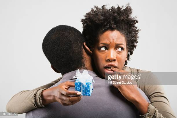 Worried African American woman hugging boyfriend with gift